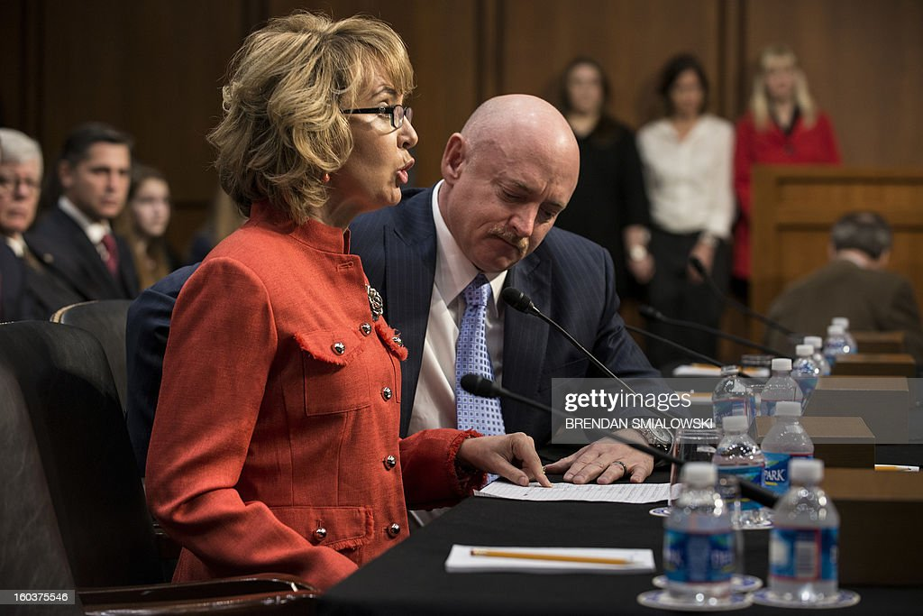 Retired Astronaut Mark Kelly, listens as his wife Arizona Rep. Gabrielle Giffords, makes a statement during a hearing of the Senate Judiciary Committee on Capitol Hill January 30, 2013 in Washington, DC. The committee held the hearing with retired Astronaut Mark Kelly, husband of former Rep. Gabrielle Giffords, Wayne LaPierre, Chief Executive Officer of the National Rifle Association, and others to testify about solutions to gun violence in the United States. AFP PHOTO/Brendan SMIALOWSKI