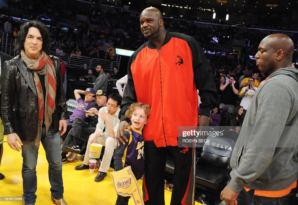 Retired basketball player Shaquille O'Neal (C) greets the son of Kiss musician Paul Stanley (L) courtside at the Los Angeles Lakers NBA match up against the Phoenix Suns at Staples Center in Los Angeles, California, February 12, 2013. The Lakers defeated the Suns, 91-85. AFP PHOTO Robyn BECK