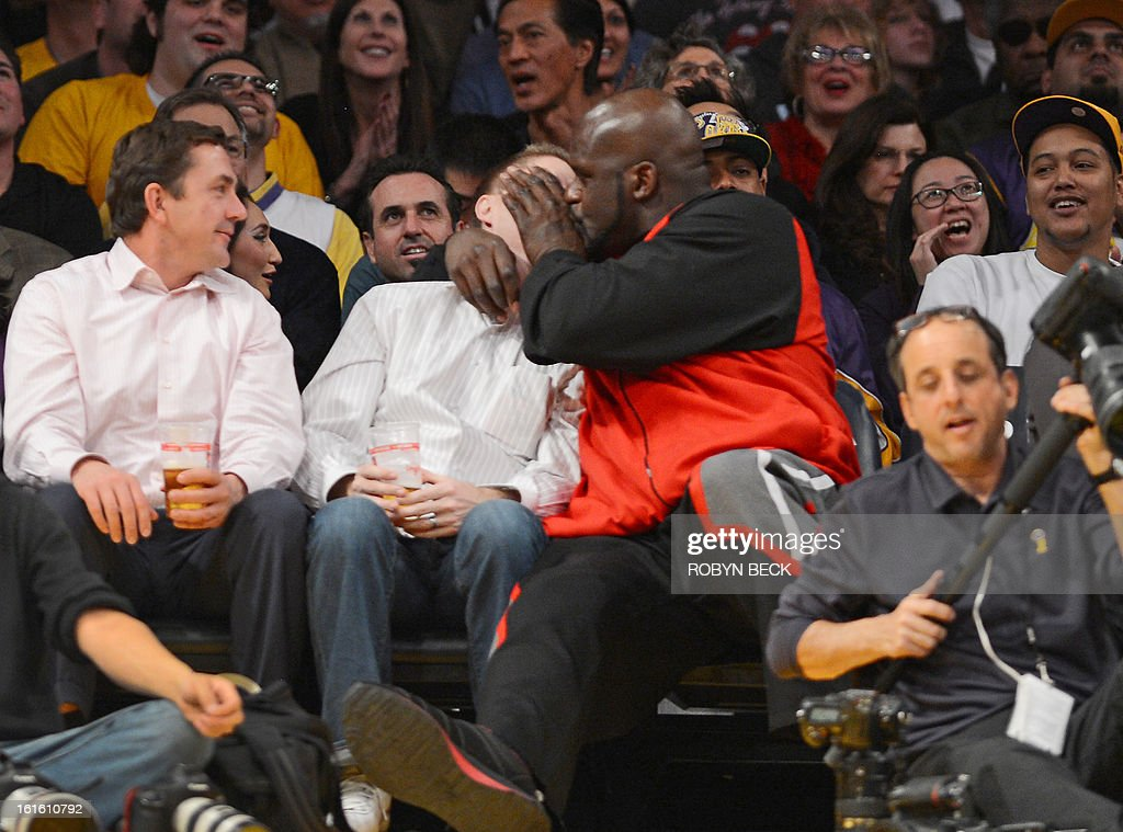 Retired basketball player Shaquille O'Neal (red and black jacket) jokingly kisses the man sitting next to him courtside at the Los Angeles Lakers NBA match up against the Phoenix Suns, at Staples Center in Los Angeles, California, February 12, 2013. The Lakers defeated the Suns, 91-85. Kobe Bryant finishes with only four points, nine assists and eight turnovers. AFP PHOTO Robyn BECK