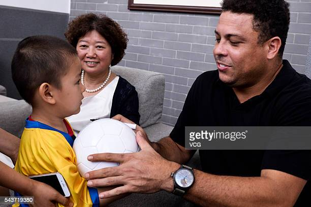 Retired Brazilian footballer Ronaldo Luis Nazario de Lima gives a football to the child during the football activity at Beijing 101 Middle School on...
