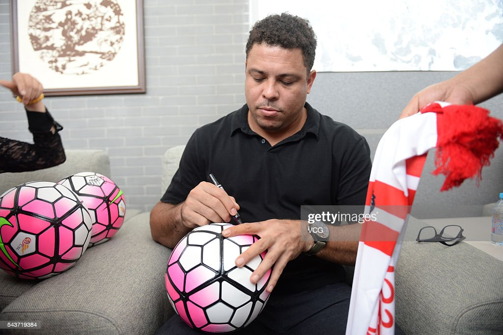 Retired Brazilian footballer Ronaldo Luis Nazario de Lima signs name on a football during the football activity at Beijing 101 Middle School on June 30, 2016 in Beijing, China. Ronaldo participated the football activity at Beijing 101 Middle School and was appointed as the football charity ambassador of China Children and Teenagers' Fund on Thursday.
