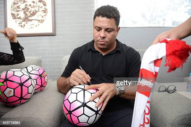 Retired Brazilian footballer Ronaldo Luis Nazario de Lima signs name on a football during the football activity at Beijing 101 Middle School on June...