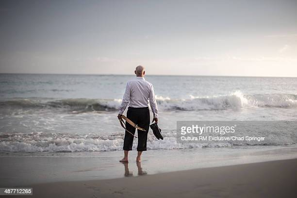 Retired businessman carrying shoes and tie, looking out to sea