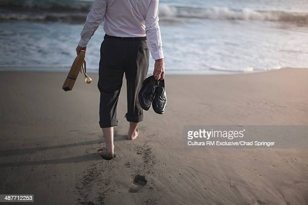 Retired businessman carrying shoes and tie, strolling to sea