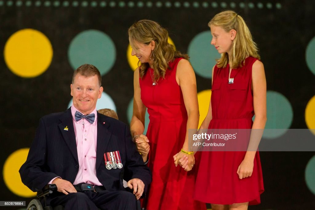 Retired Captain Trevor Greene of the Canadian Armed Forces is joined onstage by his family during the opening ceremonies of the Invictus Games in Toronto, Ontario, September 23, 2017. Green was nearly killed in Afghanistan by an axe wielding assailant who struck him in the head. / AFP PHOTO / Geoff Robins