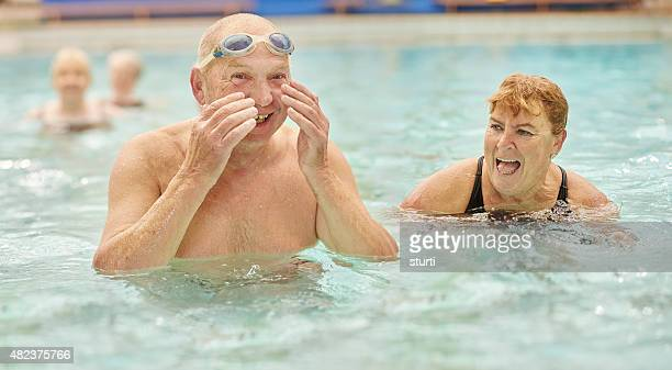 retired couple having fun at the swimming pool