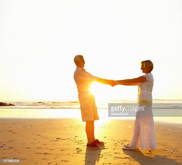 couple de retraités tenant les uns les autres à la main sur la plage