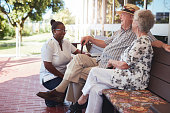 Portrait of loving retired couple relaxing on a bench outside their house with a female nurse sitting by. Caucasian elderly man and woman sitting relaxed on a bench with home caregiver at old age home