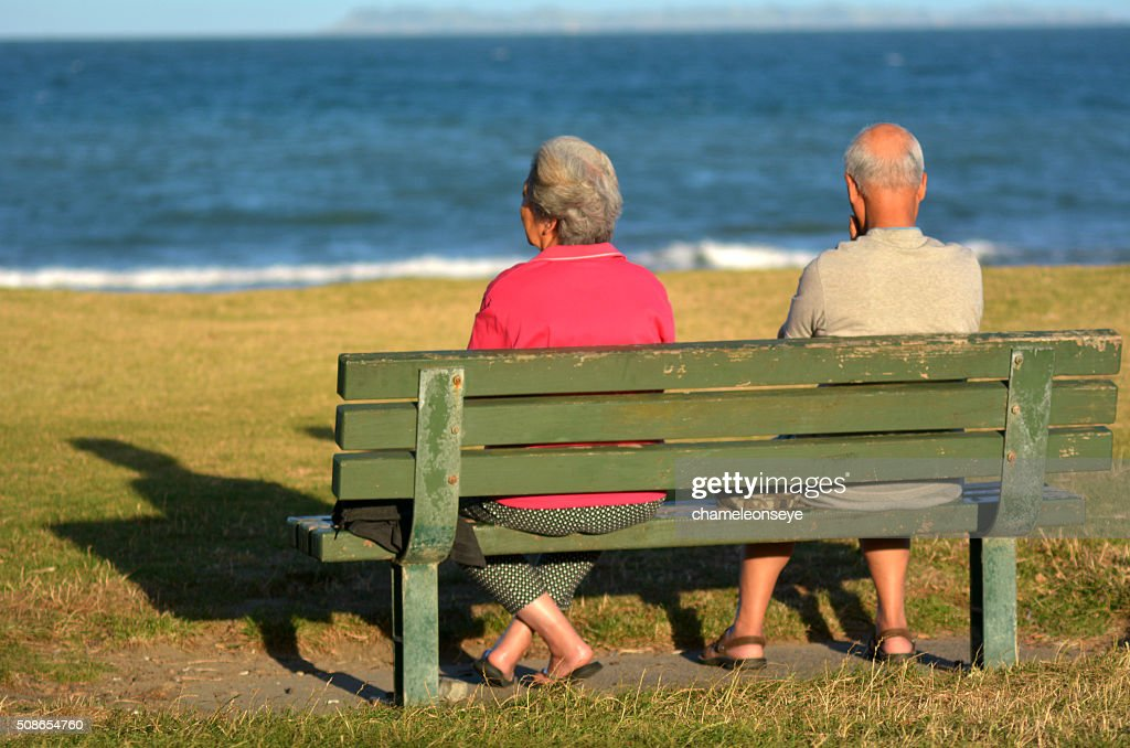 Retired couple sit on a bench : Stock Photo