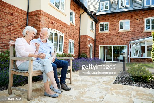 Retired Couple Sitting On Bench With Hot Drink In Assisted Living Facility : Foto de stock