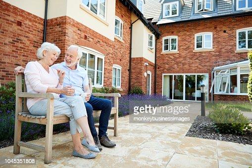 Pareja de jubilados sentados en Banco con bebida caliente en instalaciones de vida asistida : Foto de stock