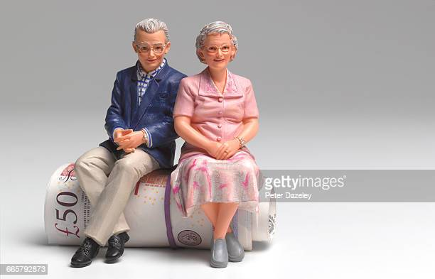 Retired couple sitting on roll of UK pounds