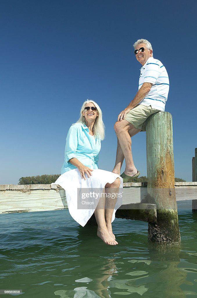 Retired couple smiling on a boat dock