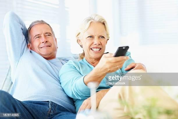 Ehemaliger Paar vor dem Fernseher während wie zu Hause fühlen.