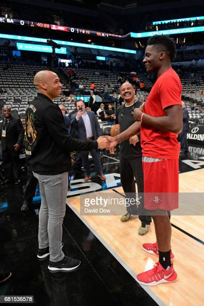 Retired French professional footballer Thierry Henry talks with John Lucas and Clint Capela of the Houston Rockets before Game Five of the Western...