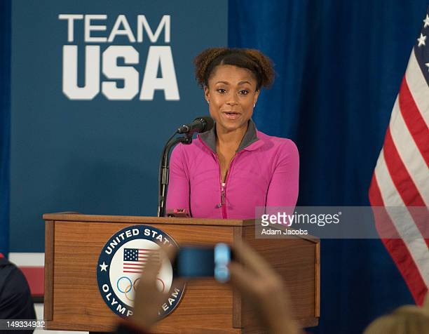 Retired gymnast Dominique Dawes introduces First Lady Michelle Obama at the University of East London on July 27 2012 in London England Michelle...