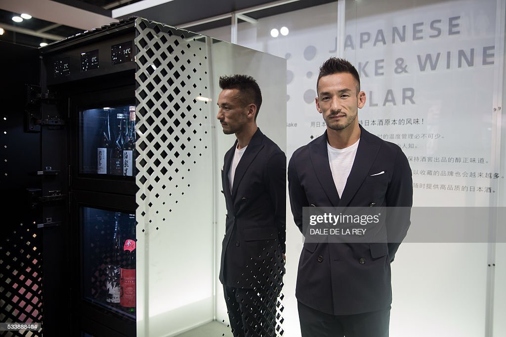 Retired Japanese football player Hidetoshi Nakata poses with a newly designed sake and wine cellar on display at Vinexpo Asia-Pacific 2016 in Hong Kong on May 24, 2016. The international wine and spirits exhibition runs from May 24 to 26. / AFP / DALE