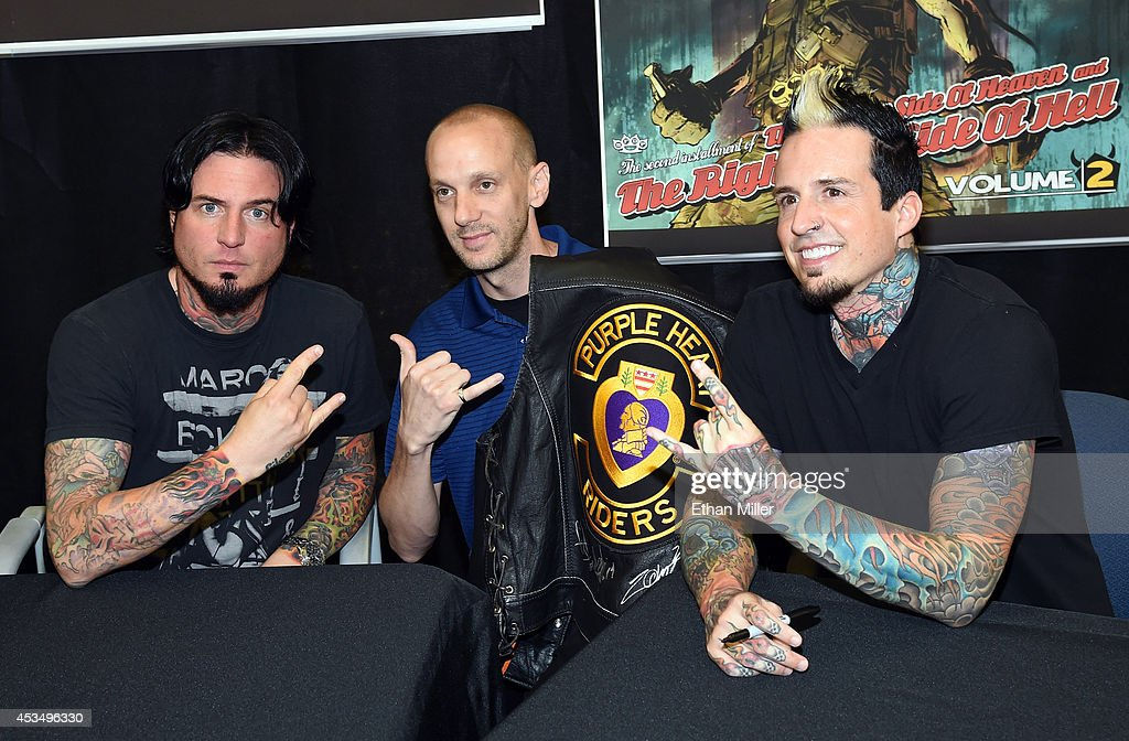 Retired Maj. Jason Regester (C) poses for a photo with guitarist Jason Hook (L) and drummer Jeremy Spencer of Five Finger Death Punch at Nellis Air Force Base as the band highlights its campaign to raise awareness about veterans suffering from post-traumatic stress disorder (PTSD), in part by launching the video 'Wrong Side of Heaven,' that deals with the subject on August 11, 2014 in Las Vegas, Nevada.