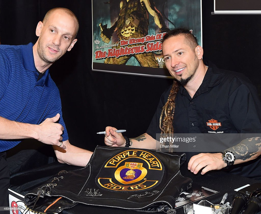 Retired Maj. Jason Regester (L) poses for a photo with guitarist Zoltan Bathory of Five Finger Death Punch at Nellis Air Force Base as the band highlights its campaign to raise awareness about veterans suffering from post-traumatic stress disorder (PTSD), in part by launching the video 'Wrong Side of Heaven,' that deals with the subject on August 11, 2014 in Las Vegas, Nevada.