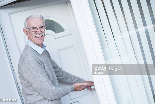Retired man opening door to his house