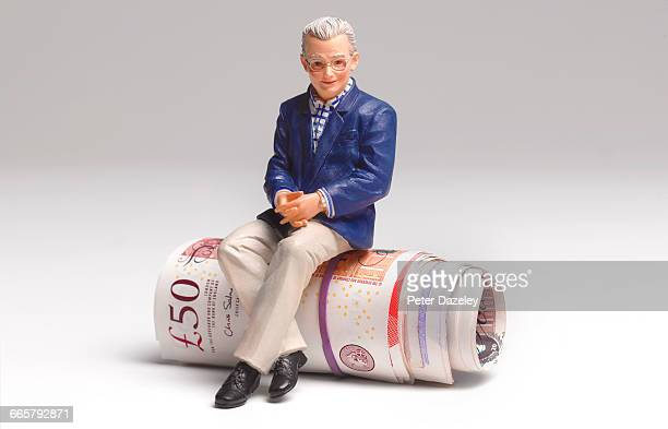 Retired man sitting on roll of UK bank notes