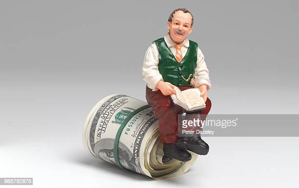 Retired man sitting on roll of US Dollars
