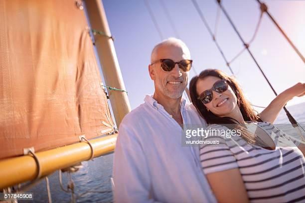À la retraite mature couple posant avec lunettes de soleil sur un Yacht