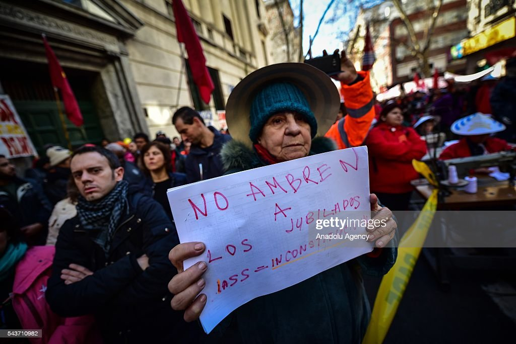 A retired old woman with a sign that says 'Do not go hungry retirees' on the march against the economic policies in Montevideo on June 29, 2016. The PIT-CNT (the only organization of unionized workers of Uruguay) today made a partial strike and marched to front the Ministry of Economy of Uruguay.