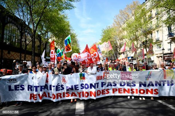 Retired persons hold a banner and unions flags as they take part in a demonstration for better pensions and the protection of their purchasing power...