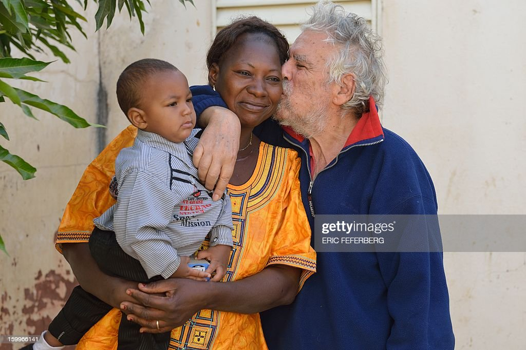 Retired Spaniard Pedro Ros, 77, poses on January 24, 2013 in the courtyard of his house in Segou, some 270 kms northeast of Bamako, with his Malian wife Genevieve and their two-year-old son Kim-Pedro. The retired economist from Barcelona is the last white resident of Segou since others fled advancing Islamists from northern Mali. With his life and family in Mali, Ros decided to stay in Segou despite the conflict because 'one has to die somewhere.'