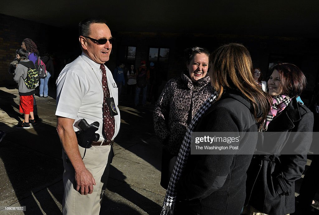 Retired state trooper Les Strawbridge chats with teachers (left to right: Jenny Gassent, Mary DiMatteo and Tracy Lesjack) at Butler Intermediate H.S. as classes were being dismissed. He wears a gun as part of the new plan to protect area students. Schools in Butler, PA are using retired state troopers to guard their schools in the wake of the Newtown, CT shootings. Photo by Michael S. Williamson/The Washington Post via Getty Images