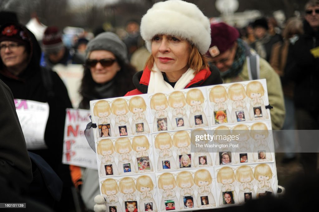 U.S. Retired teacher Lisa Church from Fairfax, VA, joins fellow gun control supporters at the Washington Monument. Church made a sign with the photographs of the victims of Newtown. 'It is time for the public to unite to protect all citizens from the violence of assault weapons,' she says.