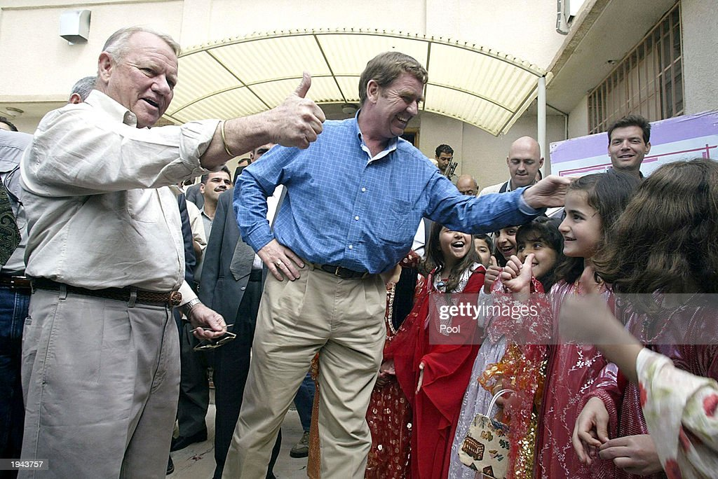 Retired US general Jay Garner who will run postwar Iraq and his deputy British General Tim Cross greet children during a visit to a primary school on...