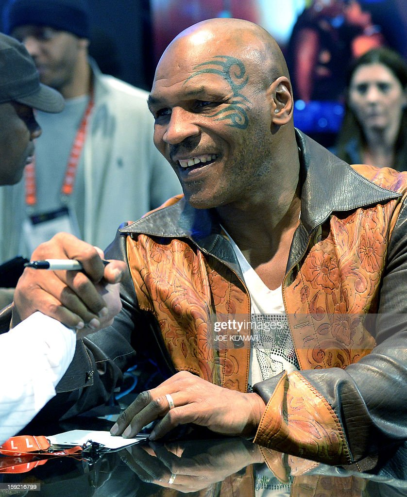 Retired US heavweight boxing Mike Tyson signs autographs at SMS Audio booth at the 2013 International CES at the Las Vegas Convention Center on January 9, 2013 in Las Vegas, Nevada. CES, the world's largest annual consumer technology trade show, runs from January 8-11 and is expected to feature 3,100 exhibitors showing off their latest products and services to about 150,000 attendees.AFP PHOTO / JOE KLAMAR