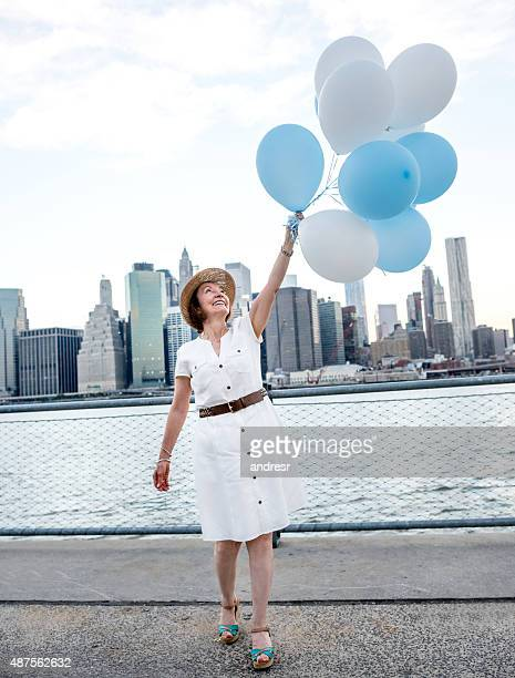 Retired woman holding balloons in New York