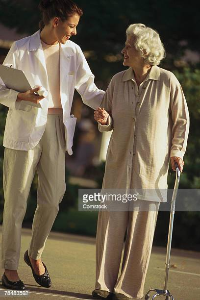Retired woman walking with healthcare professional