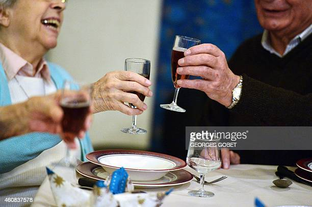Retirees raise their glasses during their Christmas eve dinner on December 24 at the St Joseph retirement home in Nantes AFP PHOTO/GEORGE GOBET