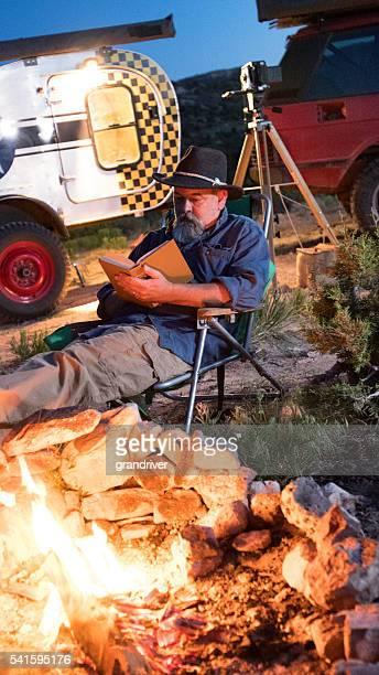 Jubilación de la caucásica hombre sentado leyendo una hoguera, Camper
