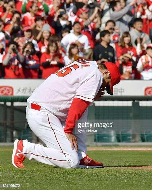 Retiring Hiroshima Carp righthander Hiroki Kuroda sinks to his knee on the mound at Mazda Stadium during his retirement ceremony in the western Japan...