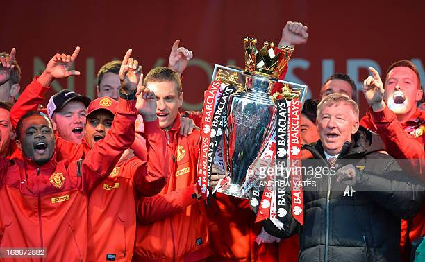 Retiring iconic Manchester United manager Alex Ferguson and his players hold the Premier League trophy outside the town hall in Manchester north west...