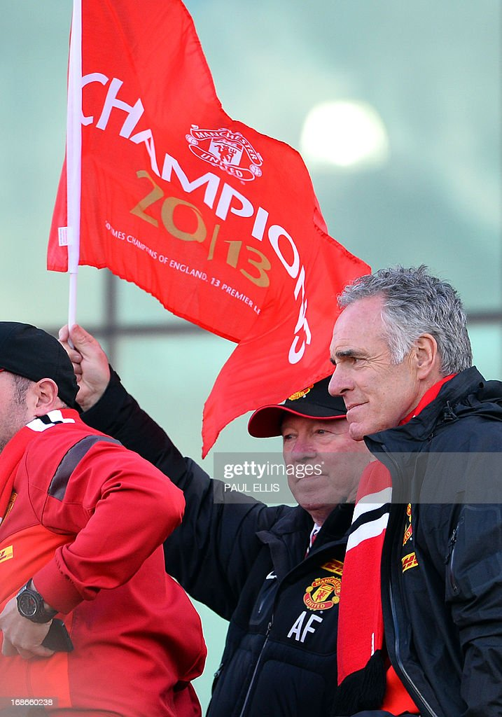 Retiring iconic Manchester United manager Alex Ferguson waves a flag onboard the champions' bus outside Old Trafford Stadium in Manchester, north west England, on May 13, 2013 as the team begins their victory parade to celebrate winning the Premier League title for the 13th time.