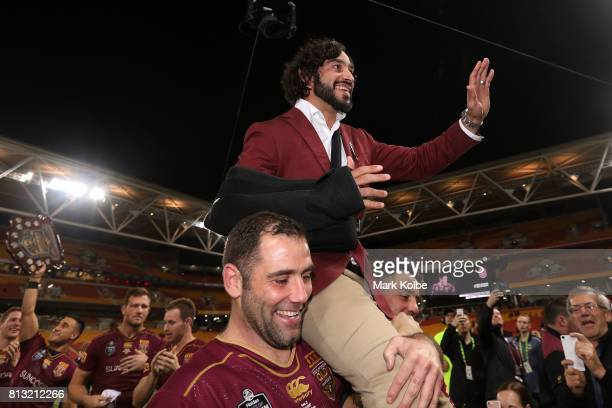 Retiring Maroons player Johnathan Thurston is chaired from the field by Cameron Smith and Cooper Cronk of the Maroons during game three of the State...