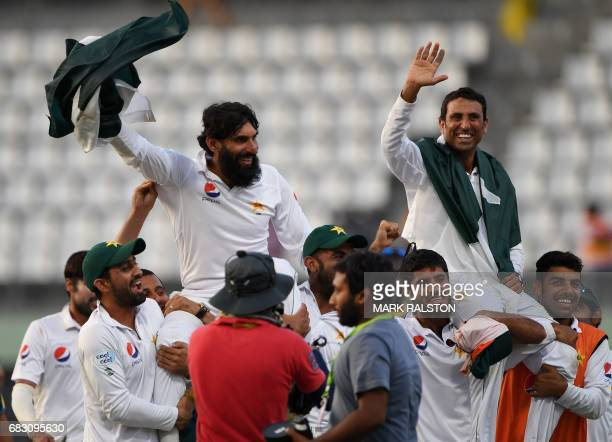 Retiring Pakistan cricket team members captain MisbahulHaq and Younis Khan are carried by teammates as they celebrate after winning the final test...