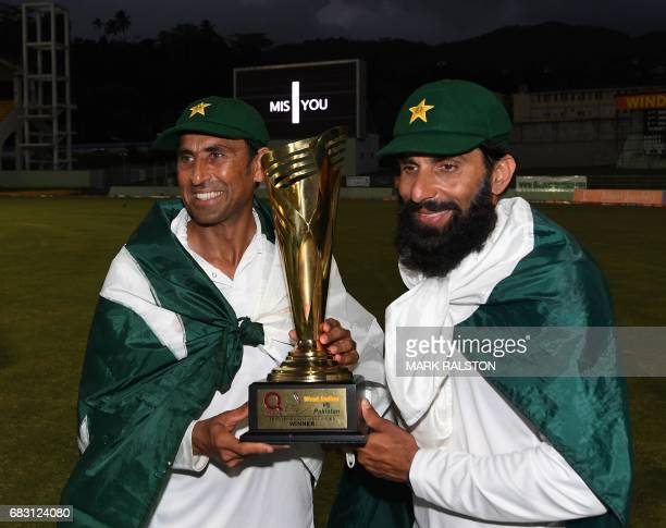 Retiring Pakistan cricket team members Younis Khan and captain MisbahulHaq celebrate with the series trophy after winning the final test match and...