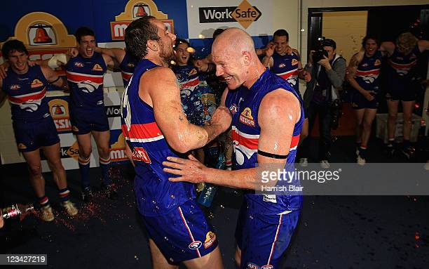 Retiring players Barry Hall and Ben Hudson of the Bulldogs celebrate in the rooms after the round 24 AFL match between the Western Bulldogs and the...
