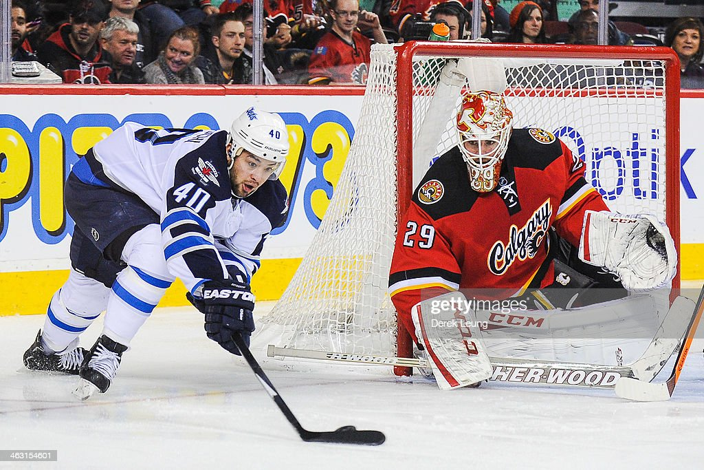 Reto Berra #29 of the Calgary Flames defends net as Devin Setoguchi #40 of the Winnipeg Jets attempts a wrap-around during an NHL game at Scotiabank Saddledome on January 16, 2014 in Calgary, Alberta, Canada. The Jets defeated the Flames 5-2.