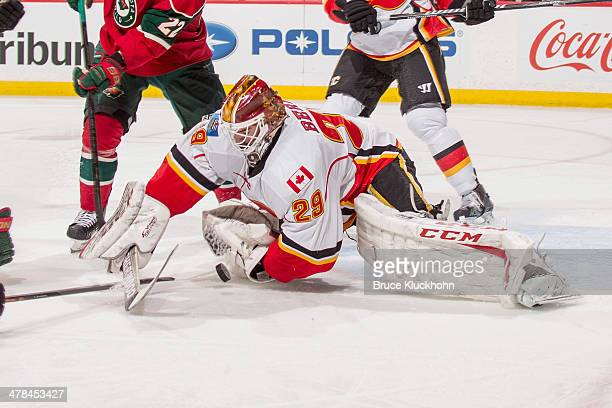 Reto Berra of the Calgary Flames dives on the puck to make a save against the Minnesota Wild during the game on March 3 2014 at the Xcel Energy...