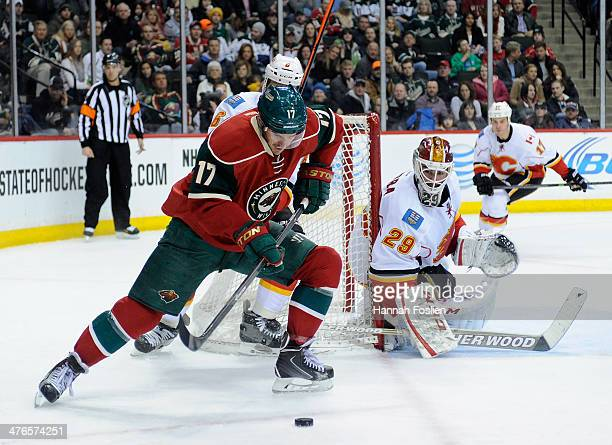 Reto Berra of the Calgary Flames looks on as Torrey Mitchell of the Minnesota Wild controls the puck during the second period of the game on March 3...
