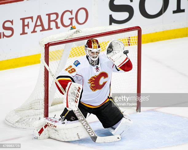 Reto Berra of the Calgary Flames makes a glove side save during the game against the Minnesota Wild on March 3 2014 at Xcel Energy Center in St Paul...