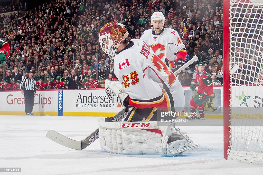 Reto Berra of the Calgary Flames makes a save against the Minnesota Wild during the game on March 3 2014 at the Xcel Energy Center in St Paul...